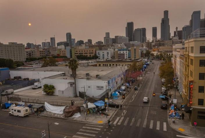 Los Angeles, CA - September 23: An aerial view of homeless encampments in Skid Row as smoke from California wildfires obscures the setting sun and skyline on Thursday, Sept. 23, 2021 in Los Angeles, CA. A federal appeals court on Thursday unanimously overturned a a judge's decision that would have required Los Angeles to offer some form of shelter or housing to the entire homeless population of skid row by October. (Allen J. Schaben / Los Angeles Times)