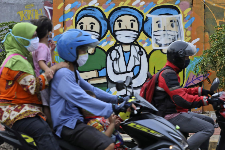 Motorists ride past a mural honoring health care workers during the new coronavirus outbreak in Jakarta, Indonesia, Thursday, May 28, 2020. (AP Photo/Dita Alangkara)