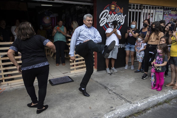 Fabio Rodolfo Vasquez, center, and his wife, Maria Moreno, dance at a promotional event outside a coffee shop, on the outskirts of Guatemala City, Saturday, Sept. 19, 2020. The couple entered an online dance contest during the new coronavirus pandemic to help them cope with the recent death of their daughter — and won it. (AP Photo/Moises Castillo)