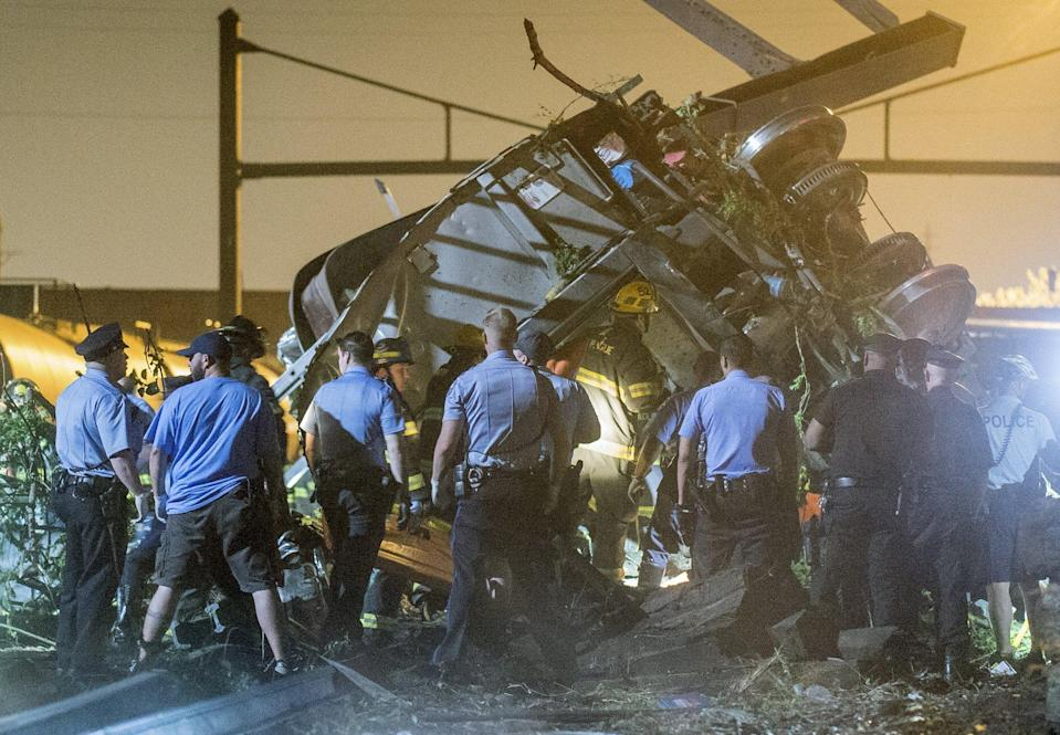 Rescue workers search for victims in the wreckage of a derailed Amtrak train in Philadelphia, Pennsylvania May 12, 2015. The Amtrak passenger train with more than 200 passengers on board derailed in north Philadelphia on Tuesday night, killing at least five people and injuring more than 50 others, several of them critically, authorities said. Authorities said they had no idea what caused the train wreck, which left some demolished rail cars strewn upside down and on their sides in the city's Port Richmond neighborhood along the Delaware River. REUTERS/Bryan Woolston TPX IMAGES OF THE DAY