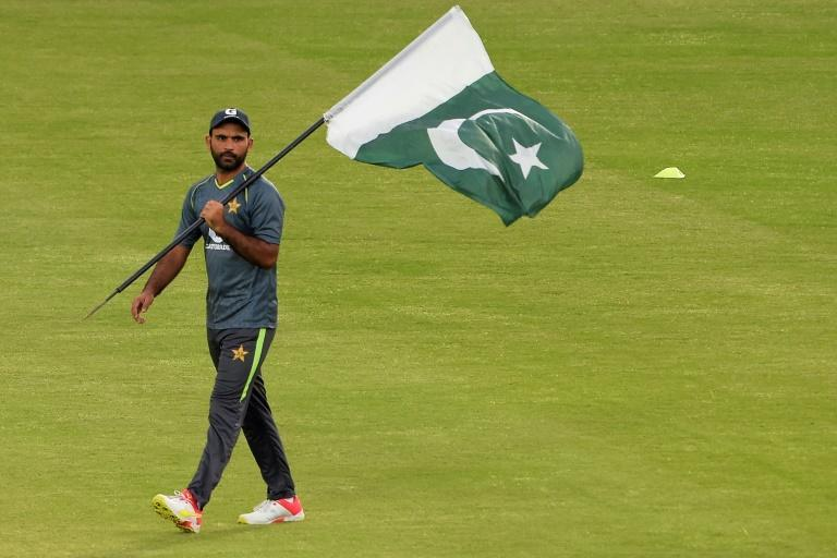 Pakistan's Fakhar Zaman carries his country's national flag upon arrival at practice for the first one-day international against New Zealand at the Rawalpindi Cricket Stadium (AFP/Farooq NAEEM)