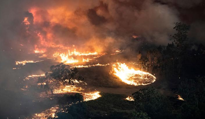 Wildfires burning across Australia's two most-populous states trapped residents of a seaside town in apocalyptic conditions on Dec. 31.