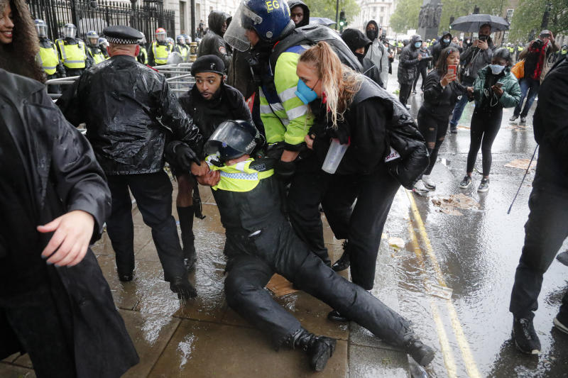 A police officer who was injured when falling of a horse during scuffles with demonstrators at Downing Street during a Black Lives Matter march in London, Saturday, June 6, 2020, is dragged by colleagues, as people protest against the killing of George Floyd by police officers in Minneapolis, USA. Floyd, a black man, died after he was restrained by Minneapolis police while in custody on May 25 in Minnesota. (AP Photo/Frank Augstein)