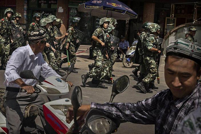 Chinese soldiers in riot gear secure the area outside the Id Kah Mosque, after Imam Jumwe Tahir was killed by assailants following early morning prayers on July 30, 2014 in old Kashgar, Xinjiang Uyghur Autonomous Region, China.