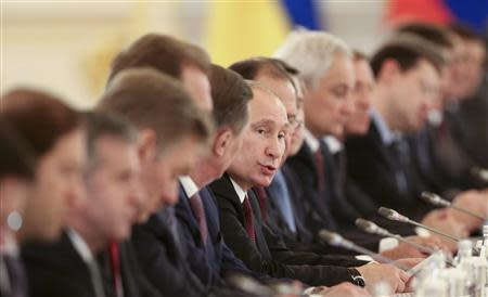 The Russian delegation, led by President Vladimir Putin (C), attend a meeting of the Russian-Ukrainian Interstate Commission at the Kremlin in Moscow, December 17, 2013. REUTERS/Sergei Karpukhin