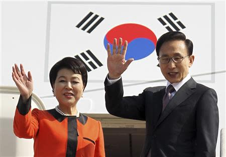 South Korean President Lee Myung-bak and his wife Kim Yoon-ok wave before they leave for Washington at a military airport in Seongnam
