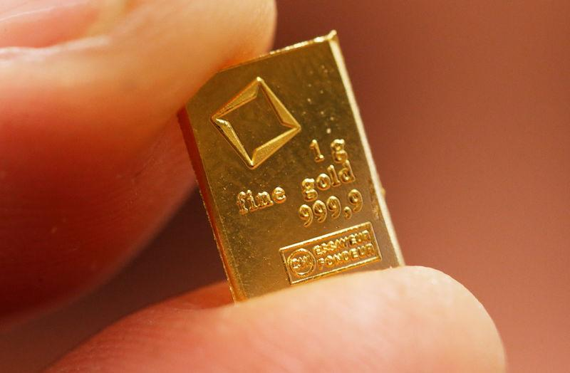 FILE PHOTO: An employee shows a 1 gram piece of a gold Combibar at a plant of gold refiner and bar manufacturer Valcambi SA in the southern Swiss town of Balerna
