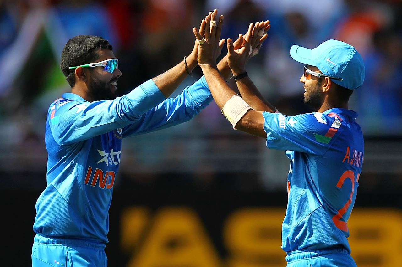 AUCKLAND, NEW ZEALAND - JANUARY 25: Ravindra Jadeja of India celebrates with teammate Ajinkya Rahane after taking the wicket of Martin Guptill of New Zealand during the One Day International match between New Zealand and India at Eden Park on January 25, 2014 in Auckland, New Zealand.  (Photo by Anthony Au-Yeung/Getty Images)