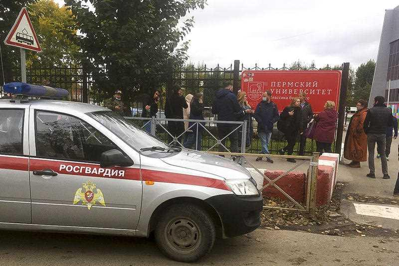 People stand behind the fence near the Perm State University with the a Posguardia (National Guardia) on the left, in Perm, Russia.