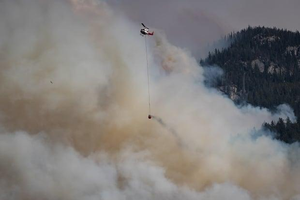 A helicopter carrying a water bucket flies past the Lytton Creek wildfire burning in the mountains near Lytton, B.C., on Sunday. The Liberals, Conservatives and NDP all touched on the wildfires during day four of the campaign. (Darryl Dyck/The Canadian Press - image credit)