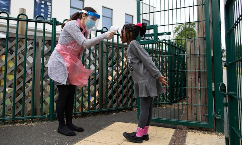 A staff member takes a child's temperature at the Harris Primary Academy Shortlands school, London.
