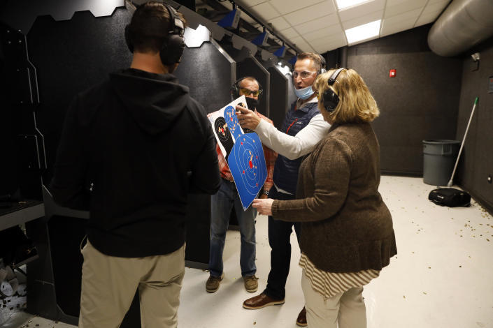 Chicago resident Ray Mandel, center, shows his target to others during a shooting session at Maxon Shooter's Supplies and Indoor Range, Friday, April 30, 2021, in Des Plaines, Ill. After a year of pandemic lockdowns, mass shootings are back, but the guns never went away. As the U.S. inches toward a post-pandemic future, guns are arguably more present in the American psyche and more deeply embedded in American discourse than ever before. The past year's anxiety and loss fueled a rise in gun ownership across political and socio-economic lines. (AP Photo/Shafkat Anowar)
