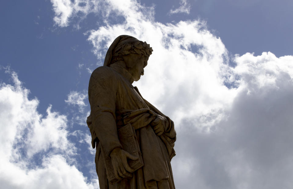 A statue of poet Dante Alighieri stands out in Santa Croce square, Florence, Italy, Thursday, May 13, 2021. Italy is honoring its great poet in myriad ways on the 700th anniversary of his death, with new musical scores and gala concerts, exhibits and dramatic readings against stunning backgrounds in every corner of the land. (AP Photo/Antonio Calanni)