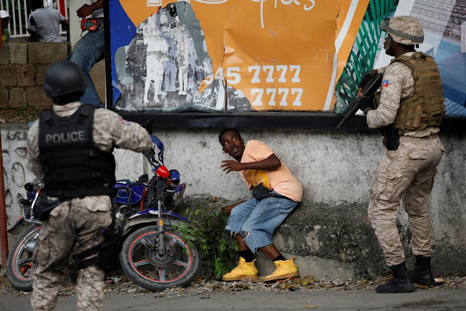 A man reacts in front of Haitian National Police
