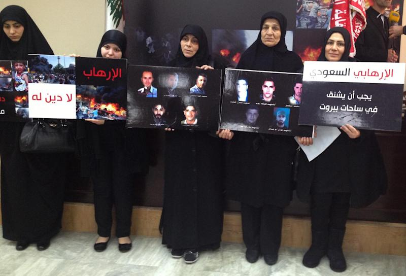 "Lebanese women whose relatives were killed at the Iranian embassy attack in Beirut last November, hold placards show portraits of their victims, as they attend a press conference, in Beirut, Lebanon, Friday, Jan. 3, 2014. DNA tests confirmed that Majid al-Majid who is in Lebanese government custody, is the alleged leader of an al-Qaida-linked group that has conducted attacks across the Middle East before shifting its focus to Syria's civil war, Lebanese authorities said Friday. Families of those killed in the embassy bombing demanded that al-Majid, who has not been charged in the attack, be tried in Lebanon and not be sent to his homeland. The Arabic placards read:"" The Saudi terrorist must hang in Beiruts' squares, right, Terrorism has no religion, left"". (AP Photo/Bassem Mroue)"