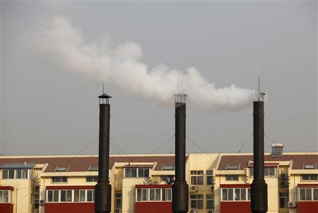 File photo of smoke billowing from chimneys of a heating plant near a residential compound in Beijing