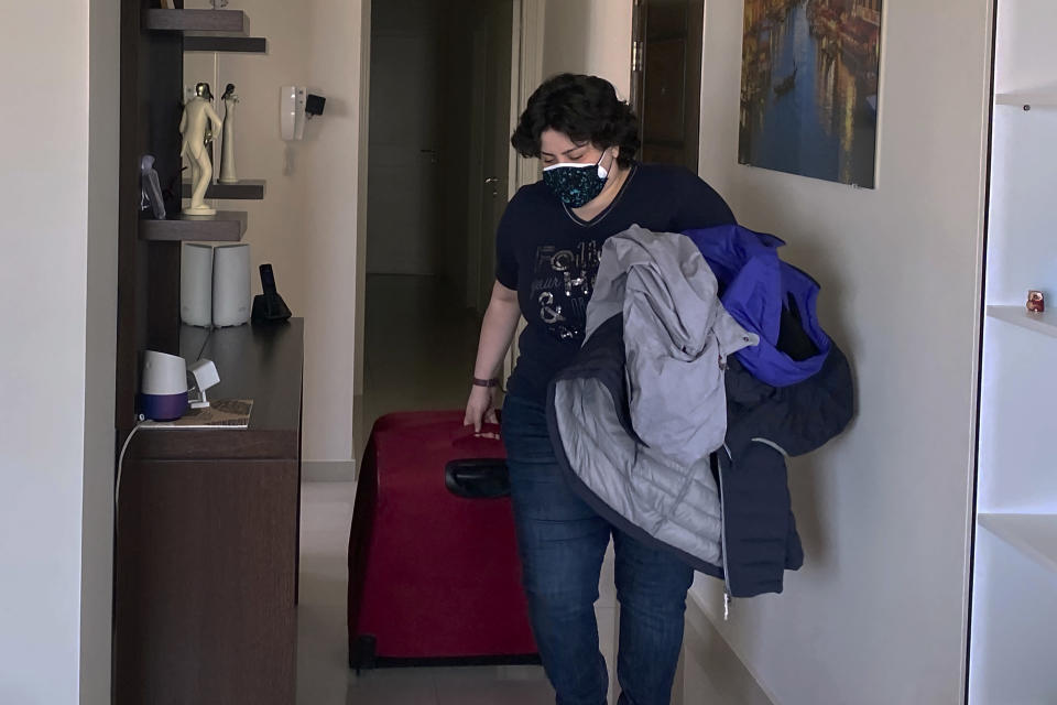 Pharmacist Rita El Khoury packs her belongings at her apartment in preparation for her move to France with her husband, in Dbayeh, north of Beirut, Lebanon, Saturday, May 8, 2021. Driven by financial ruin, collapsing institutions, hyperinflation and rapidly rising poverty, the 35-year-old pharmacist is among thousands of young and middle-aged professionals who have left or are leaving the country in the latest wave of Lebanese immigration. (AP Photo/Zeina Karam)