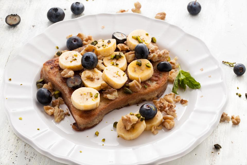 Low angle of French Toast with bananas on white wooden board