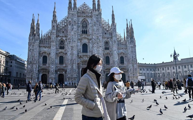Tourists wear face masks as they walk across the Piazza del Duomo in Milan - Andreas Solaro/AFP
