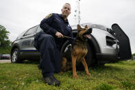 Virginia State Police K-9 officer Tyler Fridley, poses with his dog Aries at State Police headquarters in Richmond, Va., Monday, May 10, 2021. Drug-sniffing police dogs from around Virginia are being forced into early retirement as the state prepares to legalize adult recreational use of marijuana on July 1. (AP Photo/Steve Helber)