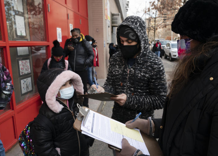 A parent, center, completes a form granting permission for random COVID-19 testing for students as he arrives with his daughter, left, at P.S. 134 Henrietta Szold Elementary School, Monday, Dec. 7, 2020, in New York. Public schools reopened for in-school learning Monday after being closed since mid-November. (AP Photo/Mark Lennihan)