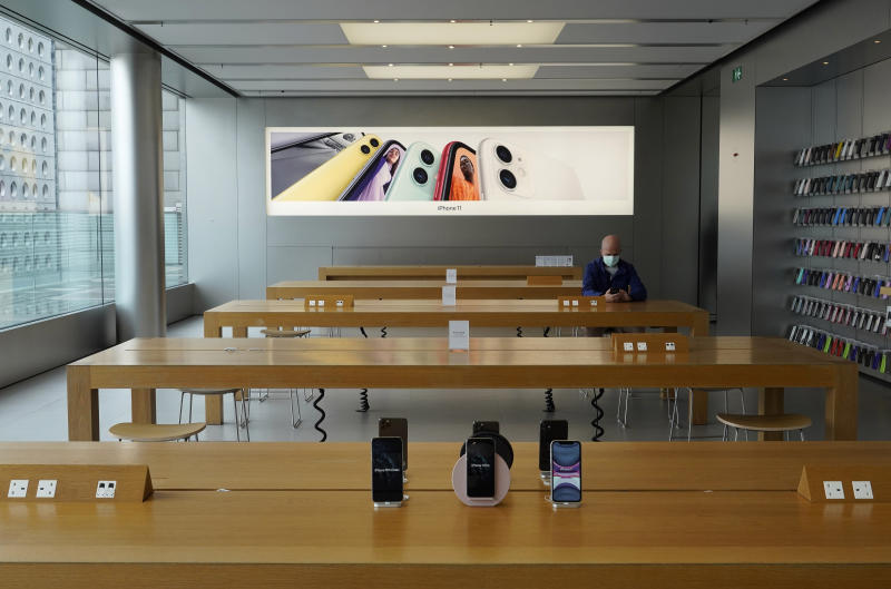 A man wearing face mask sits at an Apple Store in Hong Kong Wednesday, April 1, 2020. For most, the coronavirus causes only mild or moderate symptoms, such as fever and cough. But for a few, especially older adults and people with existing health problems, it can cause more severe illnesses, including pneumonia. (AP Photo/Vincent Yu)