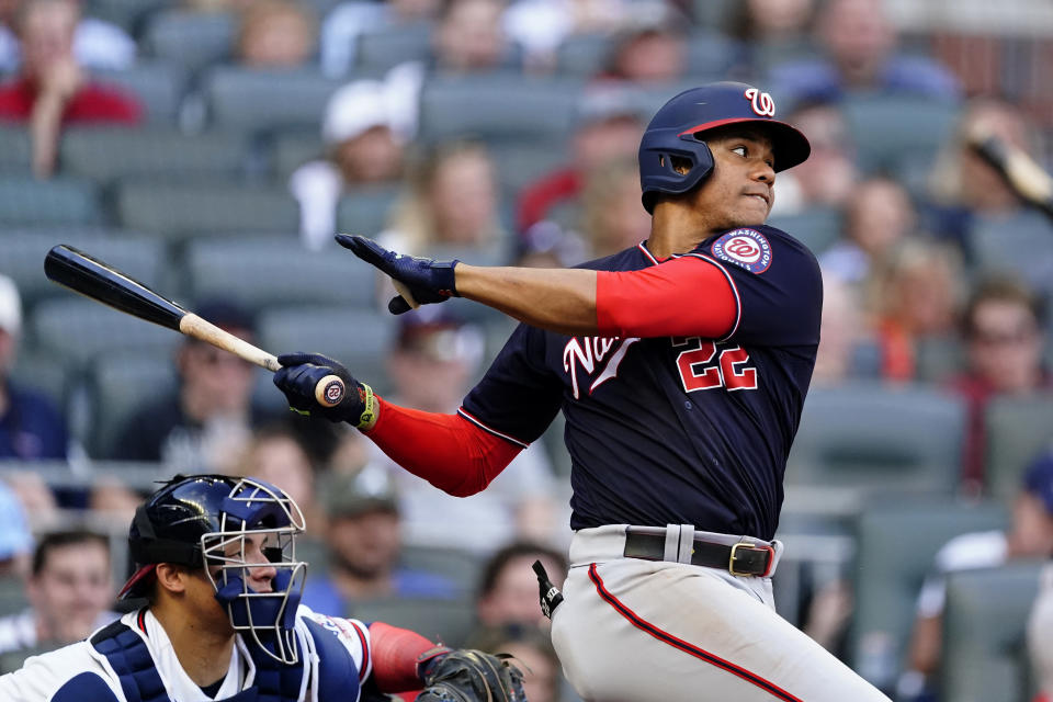 Washington Nationals' Juan Soto (22) follows through on a base bit in the fifth inning of a baseball game against the Atlanta Braves, Monday, May 31, 2021, in Atlanta. Braves catcher William Contreras, left, looks on. (AP Photo/John Bazemore)