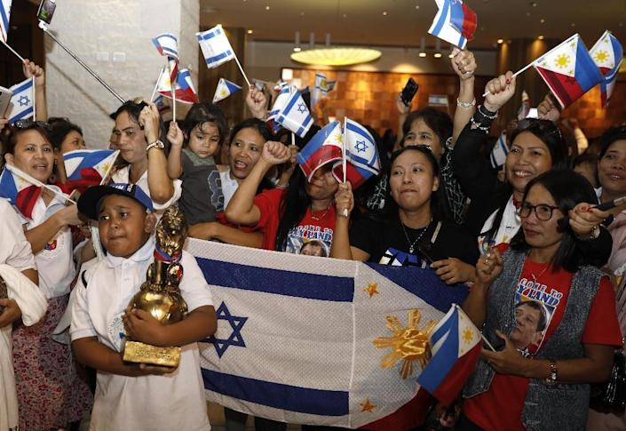 Filipinos wave their flag and the Israeli one as they wait for Philippine President Rodrigo Duterte to arrive in Israel for an official visit, on September 2, 2018 (AFP Photo/MENAHEM KAHANA)