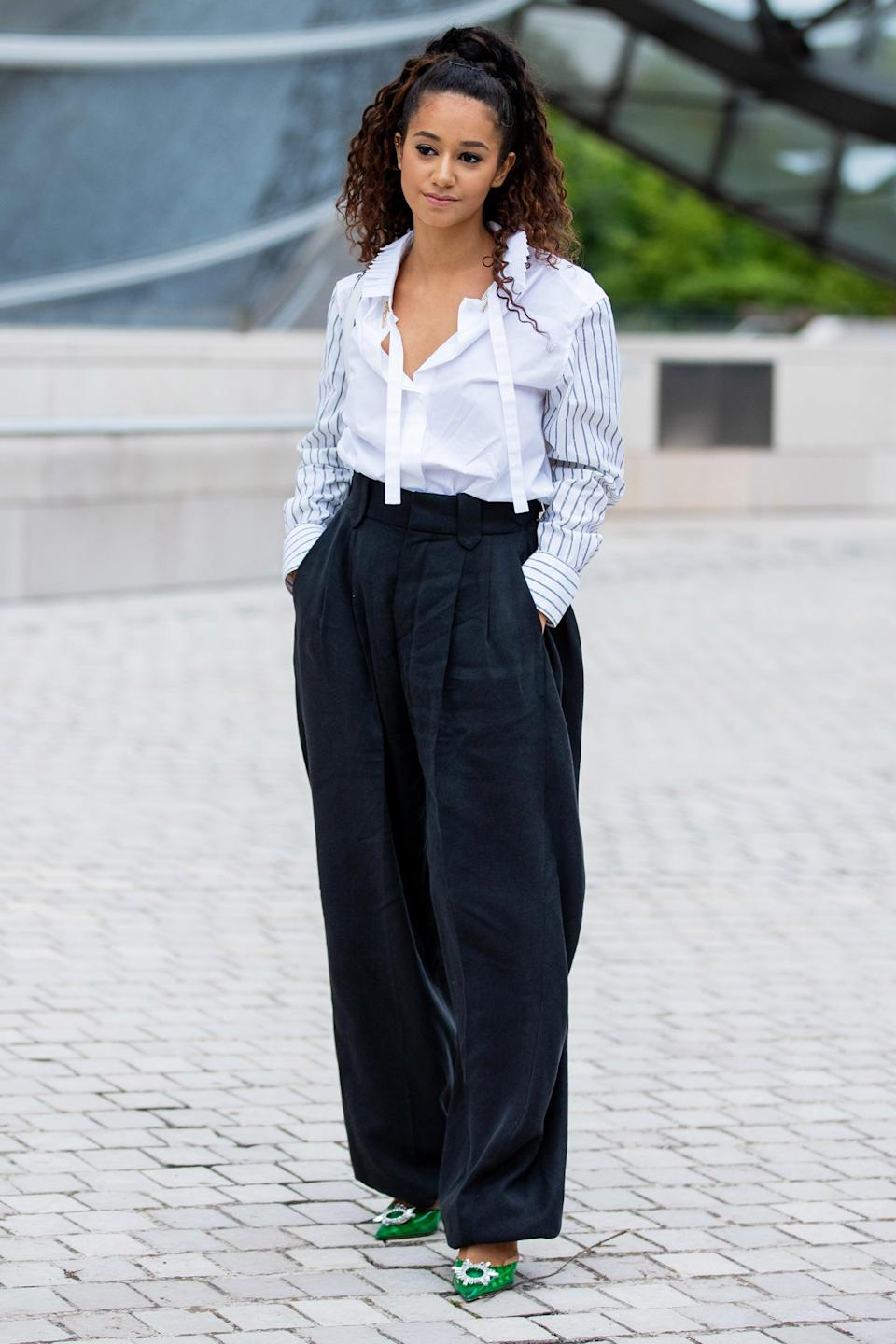 """Vlogger Léna Mahfouf added a pop of colour to her classic shirt-and-trouser combo with green pumps. <span class=""""copyright"""">Photo: Christian Vierig/Getty Images.</span>"""