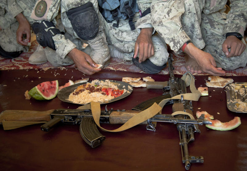 Afghan National Police lay down their guns during lunch time at their base in Marjah, Helmand Province, Afghanistan, Friday, Oct 19, 2012. Afghanistan's police are routinely targeted by insurgent attacks in southern Afghanistan, one of the deadliest regions in the country. (AP Photo/Anja Niedringhaus)