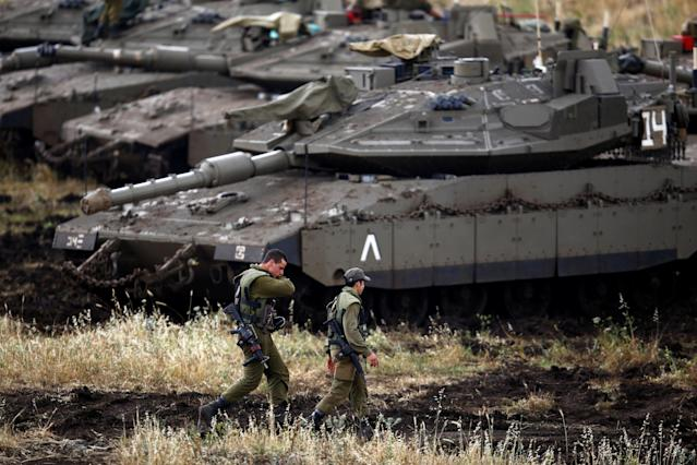 <p>Israeli soldiers walk next to tanks near the Israeli side of the border with Syria in the Israeli-occupied Golan Heights, Israel, May 9, 2018. (Photo: Amir Cohen/Reuters) </p>