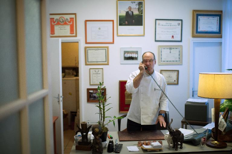 French Elysee presidential palace chef, Bernard Vaussion, speaks on the phone during his last day before retiring on October 31, 2013 at the Elysee palace in Paris