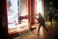 A demonstrator smashes a shop window during a protest condemning the arrest of rap singer Pablo Hasél in Barcelona, Spain, Saturday, Feb. 20, 2021. A fifth night of peaceful protests to denounce the imprisonment of a Spanish rap artist once more devolved into clashes between police and fringe group members who set up street barricades and smashed storefront windows in Barcelona. (AP Photo/Joan Mateu)