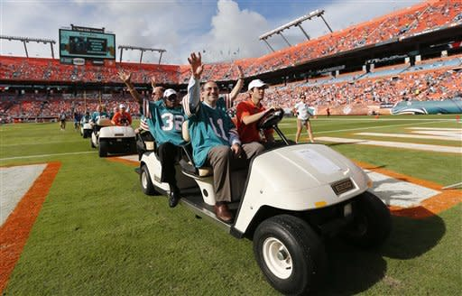 Members of the 1972 undefeated Miami Dolphins arrive to be honored during half time of an NFL football game against the Jacksonville Jaguars, Sunday, Dec. 16, 2012, in Miami. (AP Photo/John Bazemore)