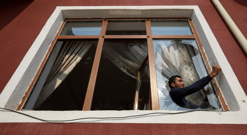 FILE PHOTO: A man removes glass from a window that was allegedly damaged by recent shelling during the fighting over the breakaway region of Nagorno-Karabakh, in the city of Tartar