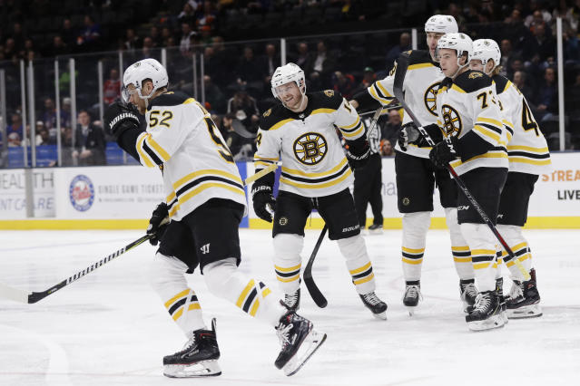 Boston Bruins' Sean Kuraly (52) skates back to his bench with teammates after scoring a goal during the first period of an NHL hockey game against the New York Islanders Tuesday, March 19, 2019, in Uniondale, N.Y. (AP Photo/Frank Franklin II)