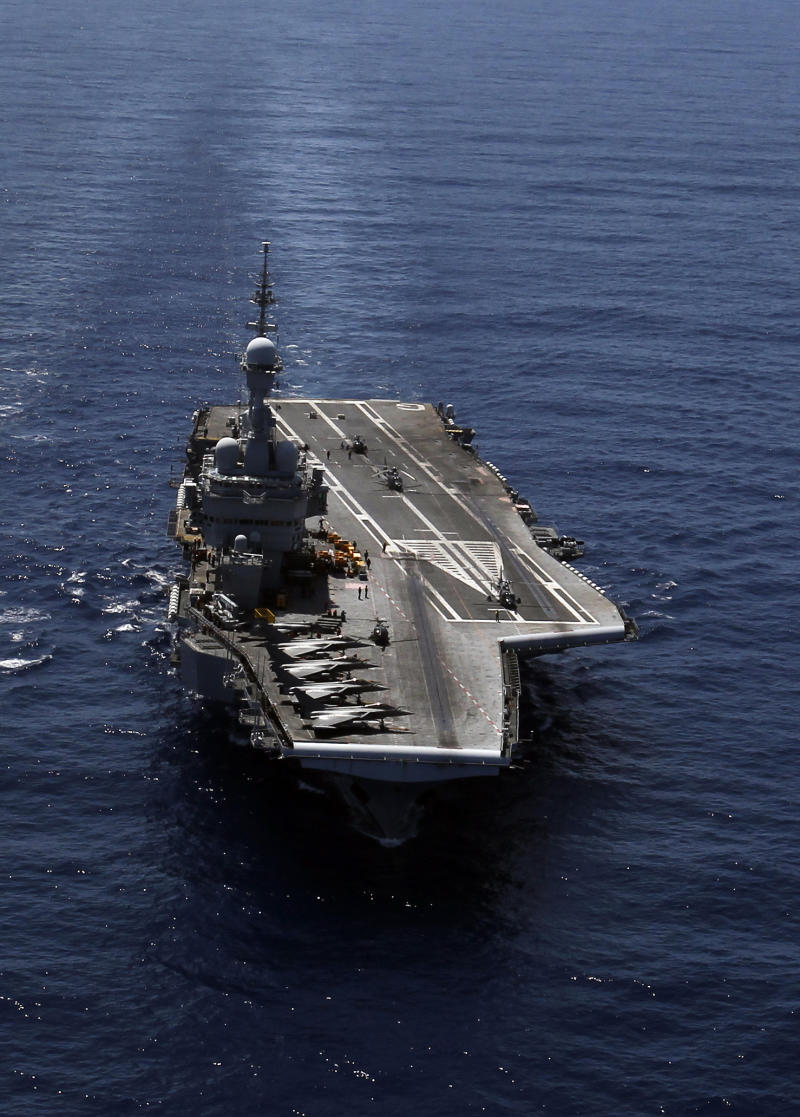 France's flagship Charles de Gaulle aircraft carrier, right, navigates in the Golf of Sirte, off the Libyan coast, Tuesday, April 12, 2011. The Charles de Gaulle is the flagship of the French fleet and the only nuclear-powered carrier outside the United States. (AP Photo/Christophe Ena)