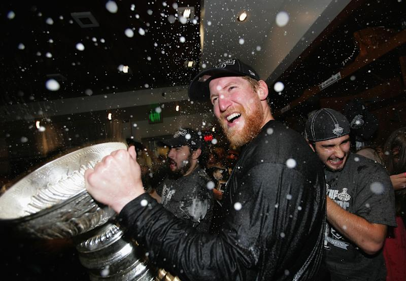 Los Angeles Kings defenseman Matt Greene (2) celebrates with the Stanley Cup in the locker room after the Kings defeated the New Jersey Devils 6-1 in Game Six of the NHL hockey Stanley Cup finals at the Staples Center Monday, June 11, 2012 in Los Angeles. The Kings won the series 4-3. (AP Photo/Dave Sandford/Pool)