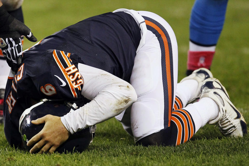 Chicago Bears quarterback Jay Cutler (6) holds his head after being sacked by Detroit Lions defensive tackle Ndamukong Suh in the first half of an NFL football game in Chicago, Monday, Oct. 22, 2012. (AP Photo/Charles Rex Arbogast)