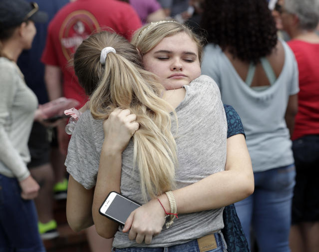 <p>Students hug outside a staging area at the First Baptist Church of Ocala as parents arrive to pick them up after a shooting incident at nearby Forest High School, Friday, April 20, 2018, in Ocala, Fla. (Photo: John Raoux/AP) </p>
