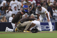 San Diego Padres Fernando Tatis Jr., second from right, is checked on by manager Jayce Tingler, left, and a trainer, second from left, after sliding into third base against the Colorado Rockies during the first inning of a baseball game Friday, July 30, 2021, in San Diego. Bobby Dickerson is at righ. (AP Photo/Derrick Tuskan)