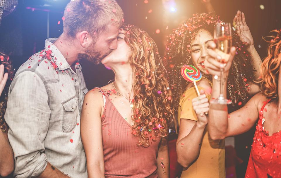 Trendy happy friends dancing at vintage night party with confetti, champagne and candy lollipop - Young people having fun inside nightclub - Youth and nightlife concept - Focus on girls faces