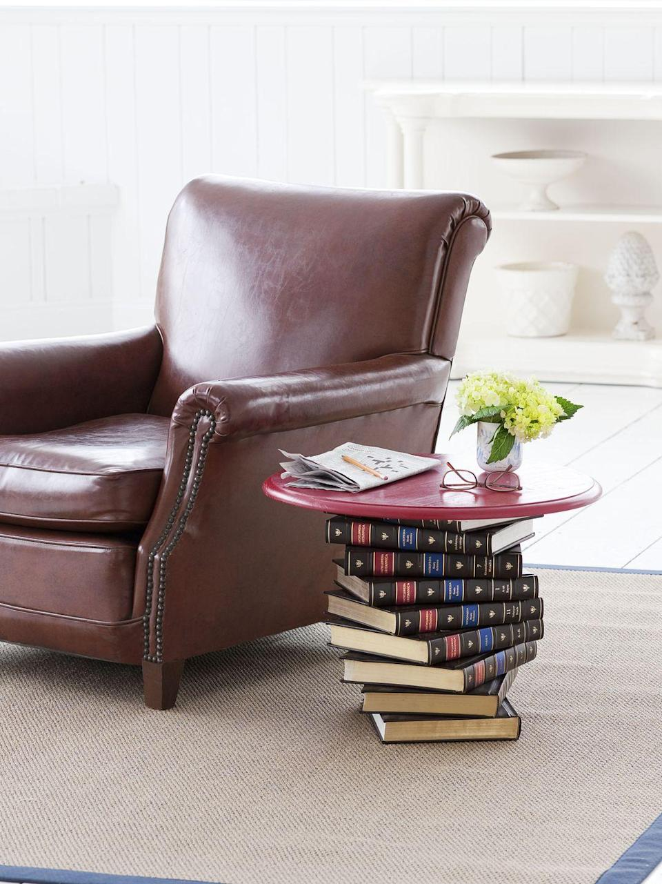 <p>Put your dusty encyclopedias to good use with this side table. To assemble, cut trim to form a box frame that fits snugly around one book, nail it to the tabletop's underside, and paint the top. Drill a hole the size of dowel through each book's center and glue the dowel to the center of the table's underside. Stack encyclopedias, lining up holes, and twisting (as shown). Skewer the dowel through the holes to secure them to the tabletop </p>