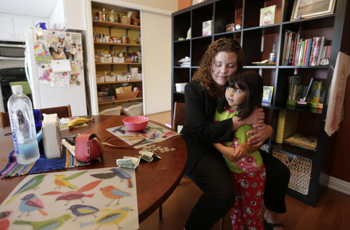 In this Sept. 26, 2012 picture, Sabina Widmann hugs her daughter Luna at their home before going to work in San Diego. (AP Photo/Gregory Bull)