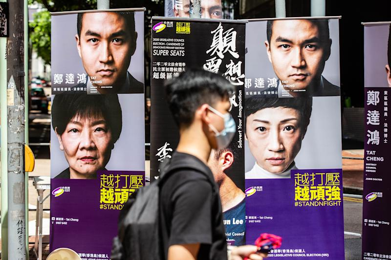 TAI KOO SHING, HONG KONG, CHINA - 2020/07/12: A man wearing a face masks walks past posters of pan-democratic candidates. In anticipation of the Legislative Council elections in September, Hong Kong citizens gathered at polling stations across the city to consolidate votes for pan-democratic candidates. Voters queued up at restaurants and submitted with paper and digital ballots. The primaries, being organized independently are technically 'unofficial' and not mandatory (nor supported) by the government, for that reason, the polling station are only set at some restaurants and not schools. (Photo by Willie Siau/SOPA Images/LightRocket via Getty Images)
