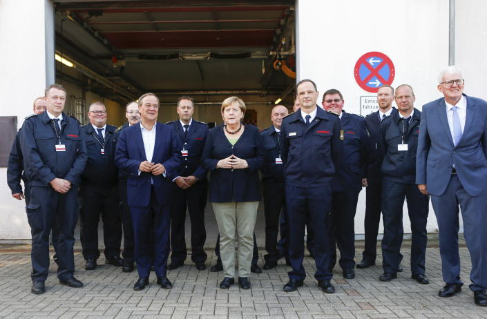German Chancellor Angela Merkel and North Rhine-Westphalia's State Premier, chairman of the Christian Democratic Union party and candidate for Chancellery Armin Laschet, center left, visit the fire station in Schalksmuehle, Germany, Sunday Sept. 5, 2021. (Thilo Schmuelgen/Pool via AP)
