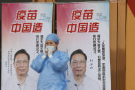 """A medical worker adjusts her mask near propaganda boards showing famed Chinese medical expert Zhong Nanshan and the words """"Vaccine China Made"""" outside vaccination center in Beijing Friday, April 9, 2021. In a rare admission of the weakness of Chinese coronavirus vaccines, the country's top disease control official says their effectiveness is low and the government is considering mixing them to give them a boost. (AP Photo/Ng Han Guan)"""