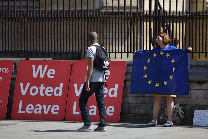 "LONDON, ENGLAND - JULY 24: A girl holding an EU flag laughs with a pedestrian as he walks past ""We voted Leave"" boards outside the Houses of Parliament in Westminster on the day Boris Johnson becomes the new Prime Minister on July 24, 2019 in London, England. (Photo by John Keeble/Getty Images)"