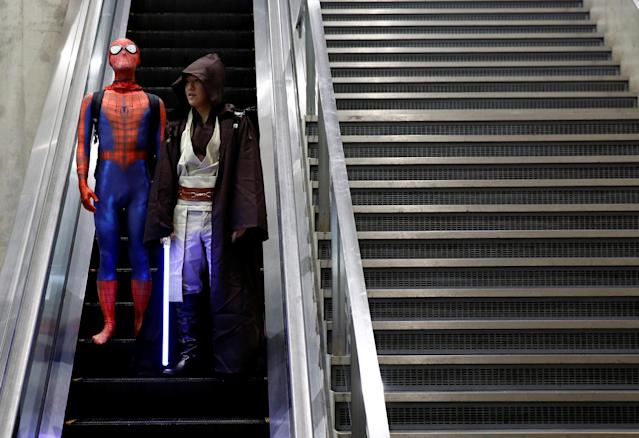 Visitors in Spider-Man and Star Wars costumes ride an escalator at Tokyo Comic Con at Makuhari Messe in Chiba, Japan December 1, 2017. REUTERS/Kim Kyung-Hoon