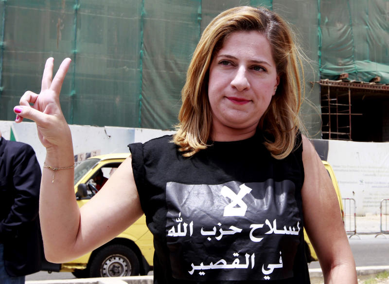 """A Lebanese activist wearing a shirt with Arabic that reads, """"no to Hezbollah weapons in Qusair,"""" flashes the victory sign, during a protest against the participation of Hezbollah in the Syrian war, at Martyrs square in Beirut, Lebanon, Sunday, June 9, 2013. A senior Lebanese military official says clashes have erupted outside the Iranian embassy in the capital between protesters opposing Hezbollah's participation in the Syrian war and unidentified locals, killing one demonstrator. (AP Photo/Bilal Hussein)"""
